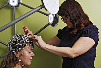 Piia Astikainen valmistelee tutkittavaa EEG-mittaukseen. Kuva: Petteri Kivimäki.